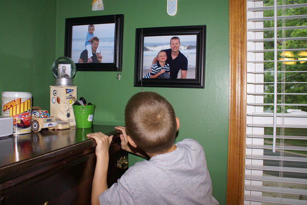 Connor looks at photos of his father, Michael Deal, who committed suicide at age 33. (Andrew Katz-Moses)