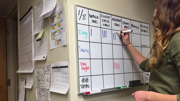 Mental health therapist Shaundra Drysdale updates daily use numbers inside a crisis support services center in Greeley, Colo.
