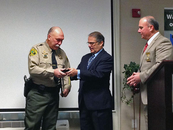 Snohomish County Sheriff's Deputy Glen Bergstrom receives the ''officer of the year'' medal from Lt. Governor Brad Owen.