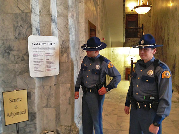 Troopers with the Washington State Patrol review the runs of what is prohibited in the Senate's public viewing galleries. Both the Senate and House have now decided to include openly-carried guns on the list of prohibited items.