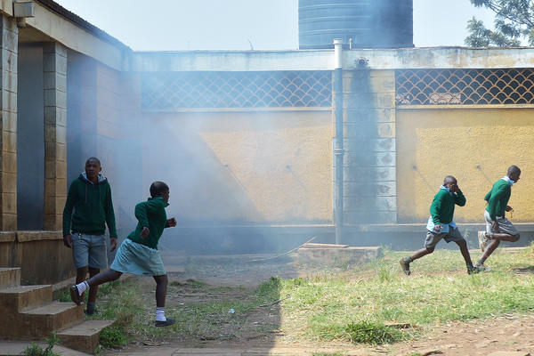 Children flee tear gas after police tried to disperse the crowd of demonstrators Monday at Langata Road Primary School in Nairobi.