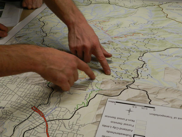 <p>Two mountain bikers examine the new trails proposed for the Ashland watershed.</p>