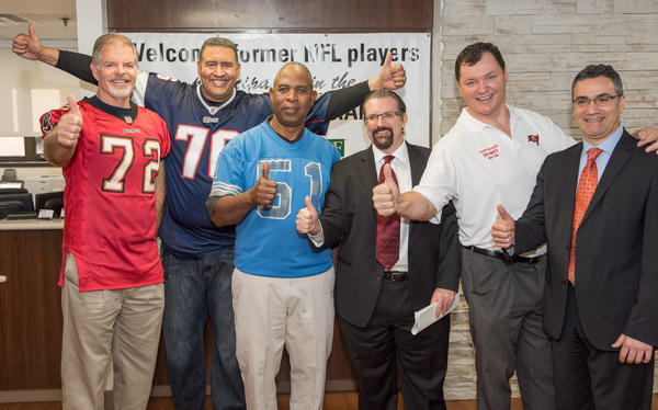 Former NFL Players (from left) Rob Taylor, Brian Holloway, James Harrell, and Jason Maniecki pose with Dr. Jon Paul Gonzalvo