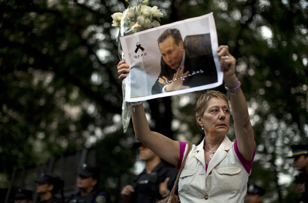 A woman holds up a portrait of late prosecutor Alberto Nisman near the funeral home where a private wake was held for him Wednesday in Buenos Aires.