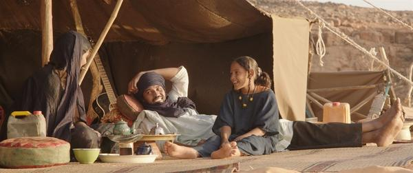 In the film <em>Timbuktu,</em> Kidane (played by Ibrahim Ahmed, center) and his wife live in a tent on a dune outside the city with their daughter (played by Layla Walet Mohamed, right) and a boy orphaned by war, raising cows.