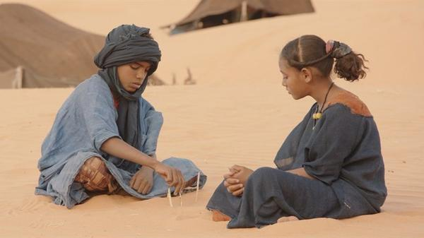 Mehdi A.G. Mohamed (left) plays Issan, the orphaned boy who lives with a family outside Timbuktu. The family decides not to leave when radical Islamists come to impose Sharia, or Islamic law.