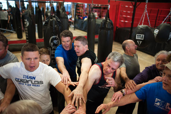 "Quaglia, center, joins a ""Rock Steady"" cheer at the end of a boxing class."