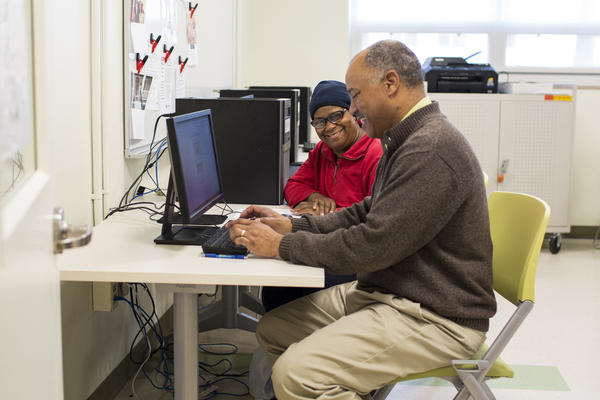 Kevin Williams (right) leads free computer classes at the Dornsife Center, which also offers career-building workshops and legal clinics to Mantua residents.