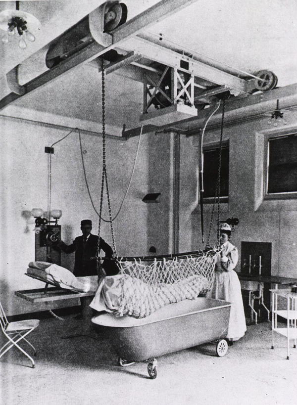 "A nurse and an orderly move a patient from his bed to a bathtub with the aid of an ""electric lift"" in 1898."