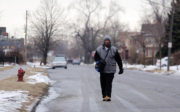 James Robertson, 56, walks to catch a bus in Detroit last month. The bus won't take him all the way to his job in Rochester Hills, so he has to walk the last eight miles.