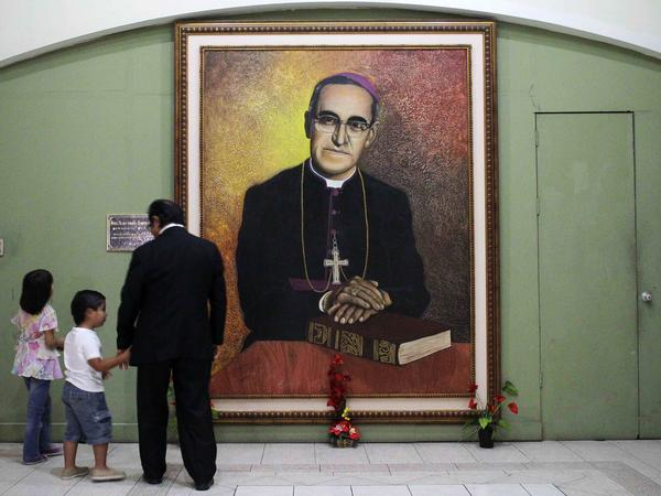 People look at a portrait of Oscar Romero at the cathedral of San Salvador, where as archbishop he resisted a brutal regime. He was murdered and the Vatican has declared him a martyr.
