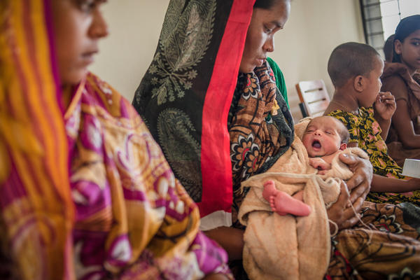 Rong Mala, 30, holds her 6-day-old child, Rakhal, as she waits to see the paramedic at a government clinic in Bangladesh.