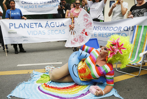"A demonstrator dressed as a bather protests against the rationing of water, outside the official residence of Sao Paulo's Governor Geraldo Alckmin in Sao Paulo, on Jan. 26. The banner behind him reads, ""Planet Water, Dry Lives."""