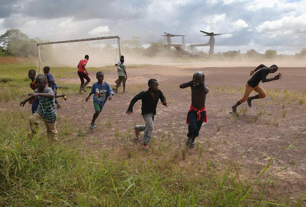Boys run from blowing dust as a U.S. Marine vehicle takes off from an Ebola treatment center under construction in Liberia in October. In the end, the centers weren't always needed, but the military's ability to ferry supplies was critical in fighting the outbreak.
