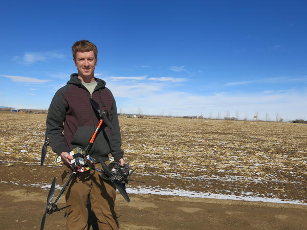 Jimmy Underhill, drone technician for Agribotix, holds a drone at a farm in rural Weld County, Colorado.