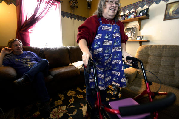 Rick King watches his wife, Cheryl, use a walker to get into the kitchen of their home in East Syracuse.