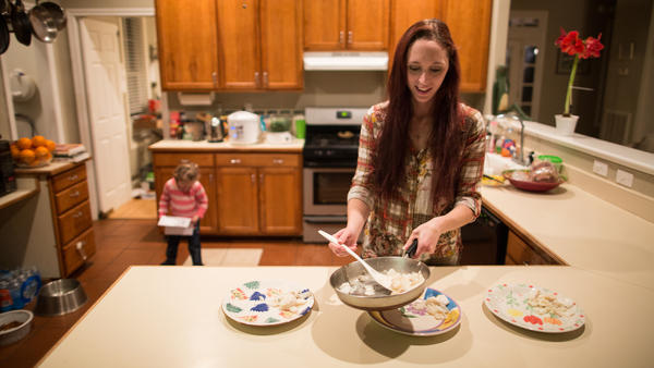 Maggie Barcellano prepares dinner in January 2014 at her father's house in Austin, Texas. Barcellano, who lives with her father, enrolled in the food stamps program while she works as a home health aide and raises her 3-year-old daughter. A study suggests that social safety nets, including food stamps, helped cushion income losses for middle- and working-class Americans during the recession.