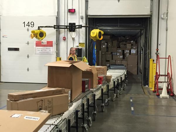 """""""Amazonians,"""" the nickname for fulfillment center workers, performing packing and loading chores, which they can do better than robots."""