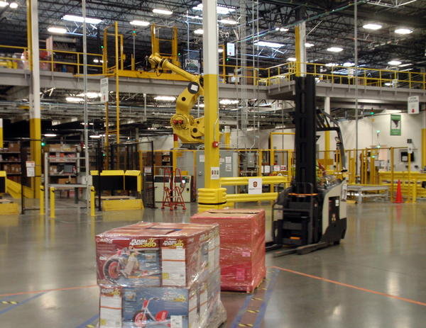 A yellow robotic arm lifts and stows heavy incoming pallets