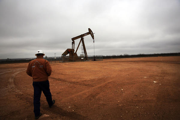 An oil well in Garden City, Texas. With prices plunging, oil companies are laying off thousands of workers.