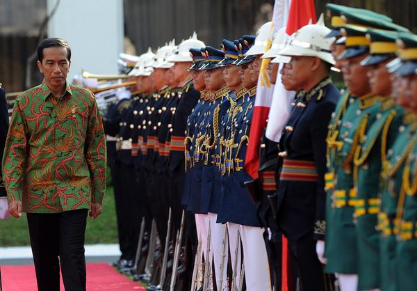 Indonesian President Joko Widodo inspects an honor guard during a visit to Manila, Philippines, on Feb. 9. Widodo's supporters see him as very different from the strongmen who have long run Indonesia. But he has dismayed some of his backers with his strong support of the death penalty.