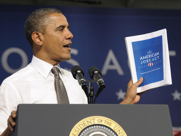 "<p>President Obama holds up a copy of his jobs bill as he speaks at Eastfield College in Mesquite, Texas. Obama is challenging a divided Congress to unite behind the bill or get ready to be run ""out of town"" by angry voters. </p>"