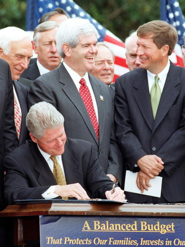 House Speaker Newt Gingrich talks with Rep. John Kasich of Ohio while President Bill Clinton signs the Balanced Budget Agreement on the South Lawn of the White House in 1997.