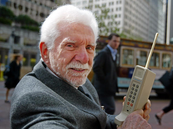 Martin Cooper holds a Motorola DynaTAC, a 1973 prototype of the first hand-held cellular telephone, in San Francisco in 2003. Cooper made the world's first public call from a cellphone in 1973.