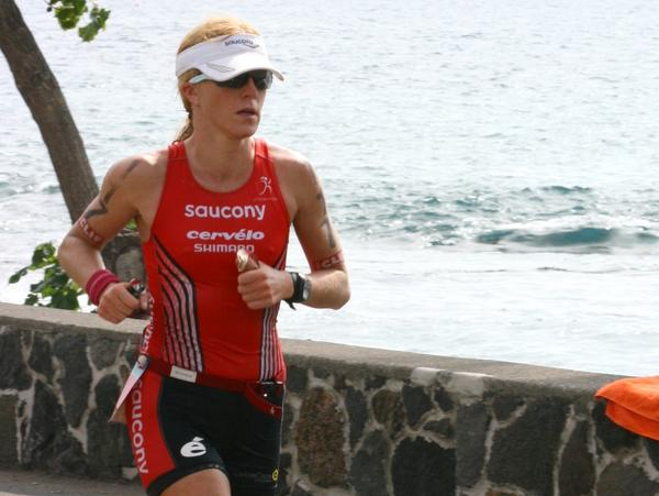 Sarah Piampiano holds two energy gels, one with caffeine and one without, as she runs in this year's Ironman World Championship.