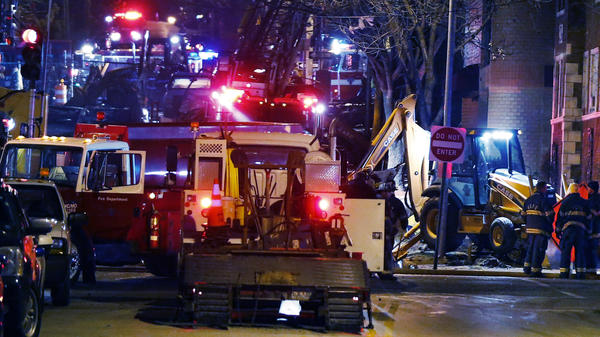 Fire fighters and utility workers at the scene of a massive gas explosion and fire Tuesday night in Kansas City, Mo.