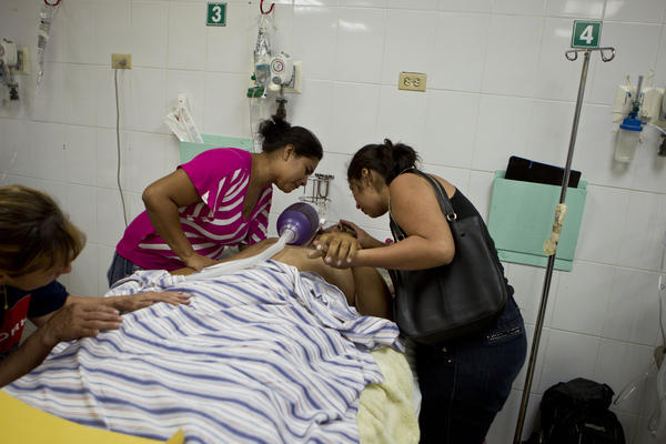 Relatives of Carlos Pineda, 30, cry over his dead body after he was shot in the head and spent an agonizing day at the emergency room of a public hospital in San Pedro Sula, on March 25.