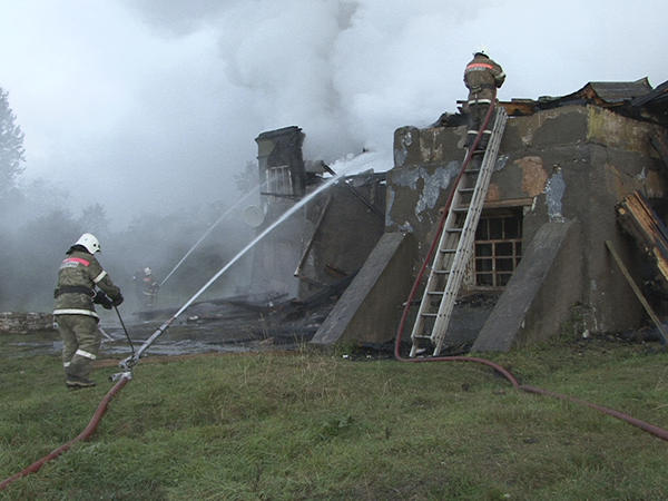 In a photo released by Russian officials in Novgorod, firefighters work at the site of a fire at a psychiatric hospital in the village of Luka on Friday.