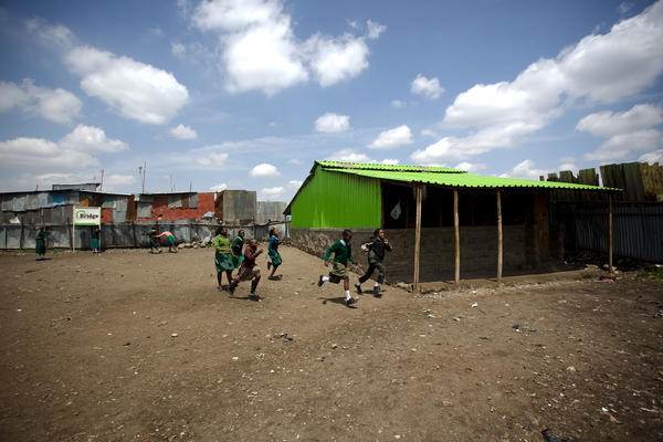Students run across the yard of the for-profit Bridge International Academy in the Nairobi slum of Mukuru kwa Njenga.