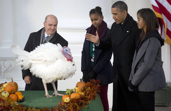 President Barack Obama, with daughters Sasha, second from left, and Malia, right, bestows a presidential pardon on Popcorn, the turkey, in a White House Thanksgiving tradition.