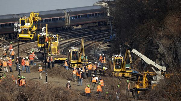 A train passes by the scene of repair efforts Tuesday at the site of a train derailment in the Bronx borough of New York.