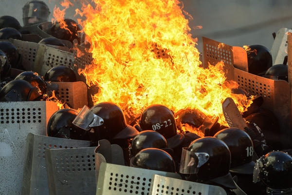 Policemen fight a fire during a clash with protesters. As of late Tuesday, at least 18 people had been killed and dozens injured.
