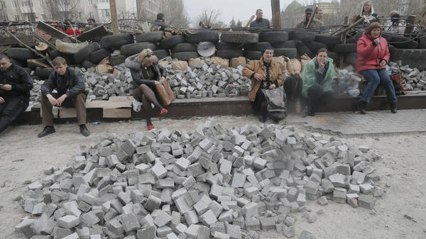 Pro-Russian activists sit at a barricade at the regional administration building in Donetsk on Wednesday. Police have been conspicuously absent at Eastern Ukraine protest sites.