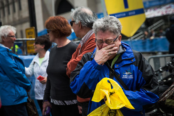 Sharon Neary, of Rochester, N.Y., cries while watching a billboard television screen in Boston broadcasting the ceremony commemorating the one-year anniversary of the 2013 Boston Marathon Bombing.