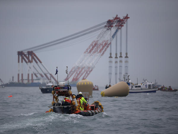 Cranes, ships and other rescue equipment are on the scene off the southern coast of South Korea, where a ferry capsized Wednesday. About 270 people, most of them high school students, remain missing.