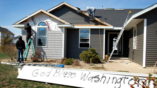 Washington, Ill., is full of both optimistic signs and lots of construction crews as the town rebuilds after a half-mile-wide tornado devastated the area in November.