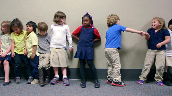 Preschool students from Nikki Jones' class at Porter Early Childhood Development Center in Tulsa line up in the hallway on their way back from outside play.