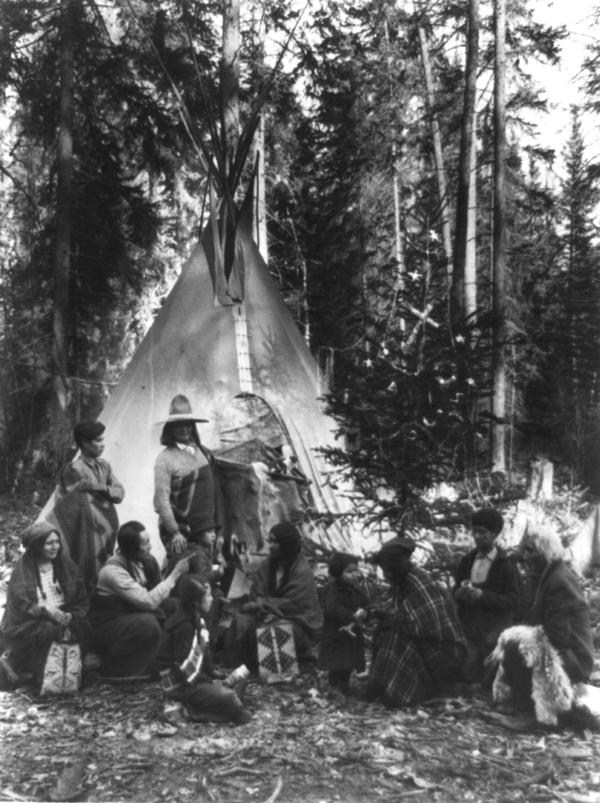 A Native American family gathers around a Christmas tree in Montana, ca. 1900-1920.