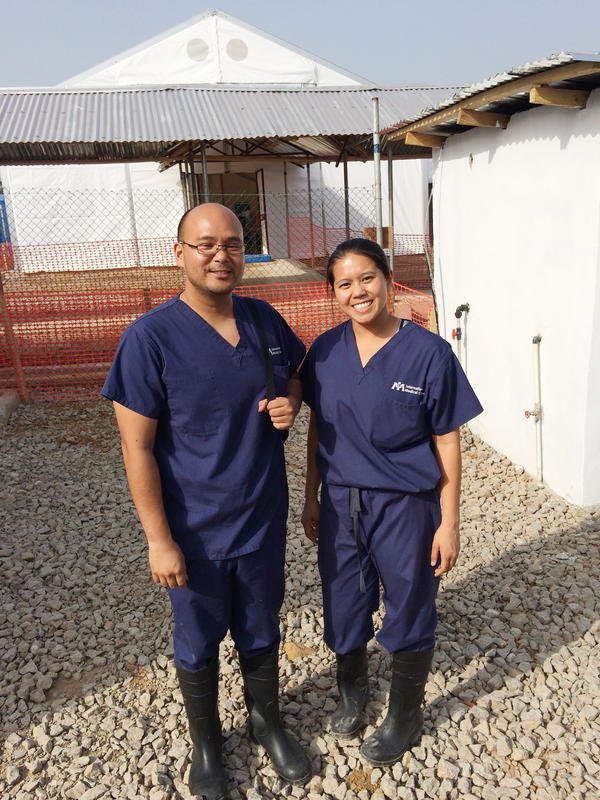 The Tran siblings stand outside an Ebola treatment center in Sierra Leone that they both helped set up.