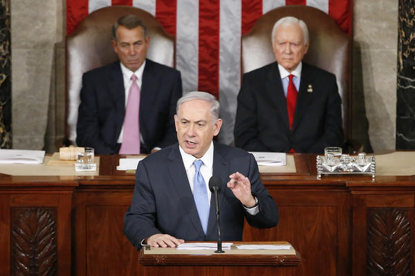 "Israeli Prime Minister Benjamin Netanyahu speaks before a joint meeting of Congress on Capitol Hill in Washington on Tuesday. Netanyahu said the world must unite to ""stop Iran's march of conquest, subjugation and terror."" House Speaker John Boehner of Ohio (left) and Sen. Orrin Hatch, R-Utah, listen."