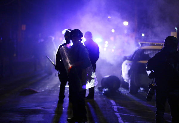 Police officers watch protesters as smoke fills the streets of Ferguson, Mo., on Nov. 25, 2014.