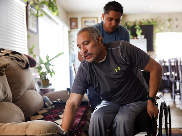 Joel Ramirez climbs back into his wheelchair with the help of Francisco Guardado, a home health aide, at his home in Rialto, Calif. Ramirez was paralyzed from the waist down in 2009 when a 900-pound crate fell on him at a warehouse. Changes to California workers' compensation laws have impacted his quality of care.
