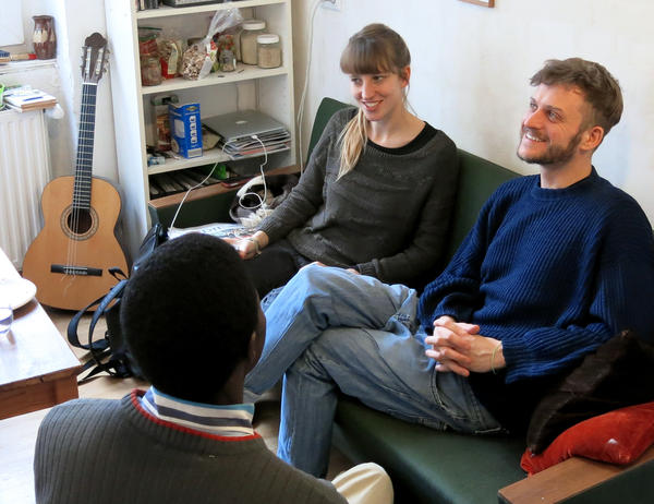 Berlin residents Mareike Geiling (left) and her boyfriend, Jonas Kakoschke, speak with their roommate, a Muslim refugee from Mali. Geiling and Kokoschke helped launch a website that matches Germans willing to share their homes with new arrivals.