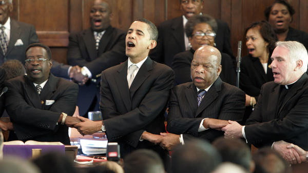 Then-Sen. Obama; Rep. John Lewis, D-Ga.; and the Rev. Clete Kiley hold hands and sing at the end of a church service in Selma, Ala., during the 2007 commemoration of Bloody Sunday.