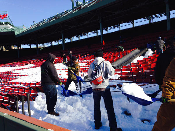 Workers clear snow from the stands at Fenway.