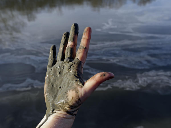Amy Adams, North Carolina campaign coordinator with Appalachian Voices, shows her hand covered with wet coal ash taken from the Dan River, which swirls in the background in February 2014. The Duke Energy spill coated 70 miles of the river with toxic sludge containing arsenic, selenium, and boron.